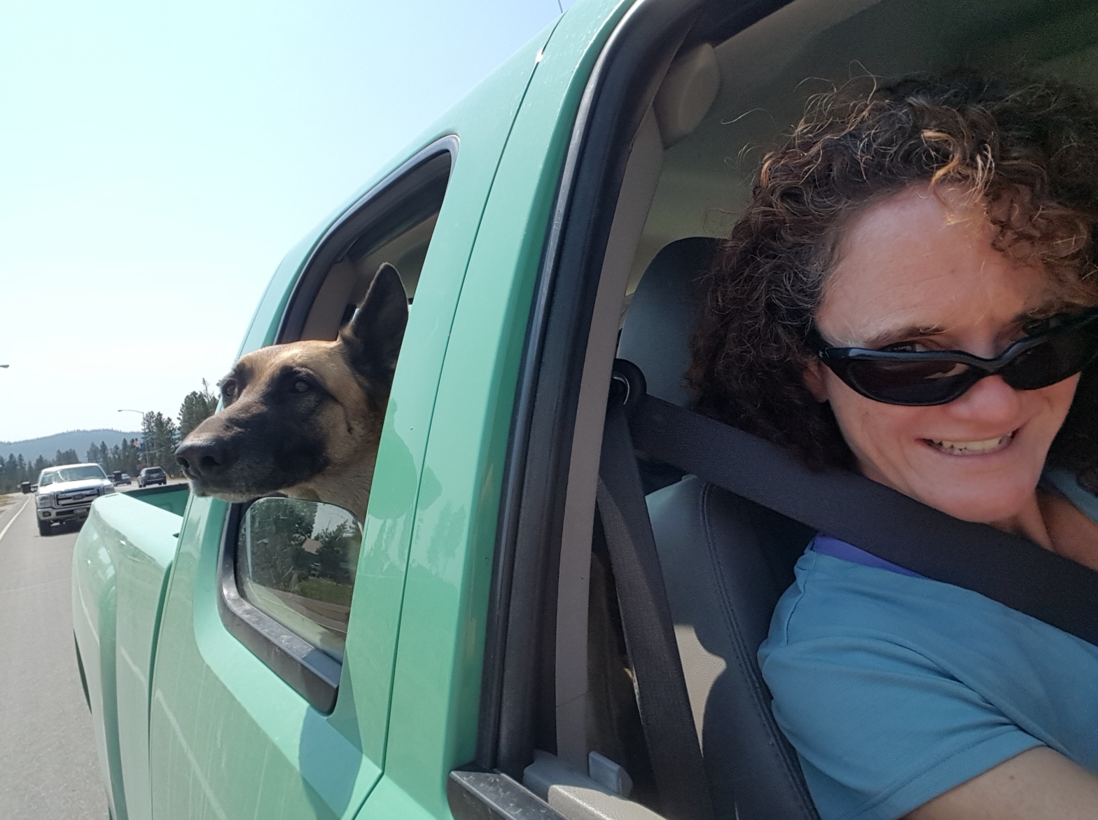 Sarah Fry leans out the passenger window of a truck and her dog's head sticks out the window behind her.